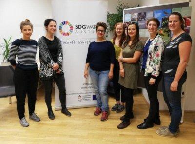 Die Teilnehmerinnen des Workshops stehen mit einem Roll-up, auf dem das Logo der Sustainable Development Goals zu sehen ist.